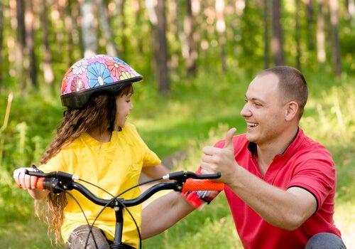 Papà insegna alla figlia ad andare in bicicletta