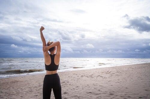 Donna fa stiramenti in spiaggia