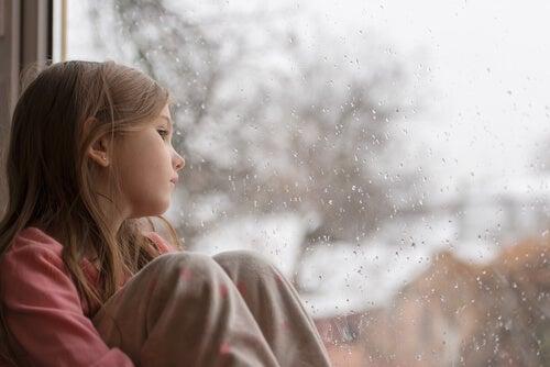 Bambina guarda fuori dalla finestra pensierosa