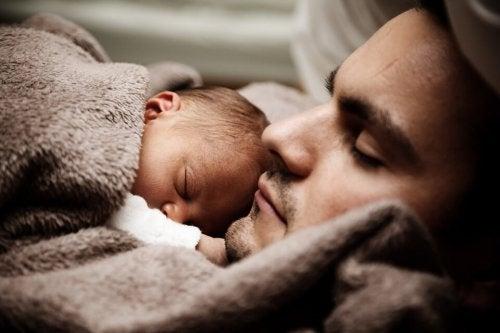 Neonato che dorme sul padre