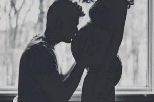 Uomo che bacia la pancia della compagna incinta