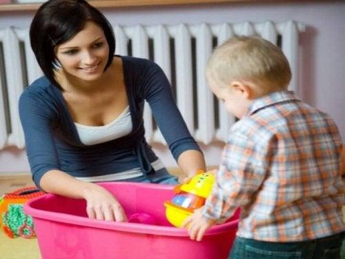 Mamma e figlio che mettono in ordine i giocattoli