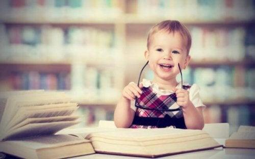 Bambina con sorride in mezzo ai libri
