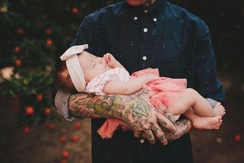 Padre tatuato tiene in braccio la figlia