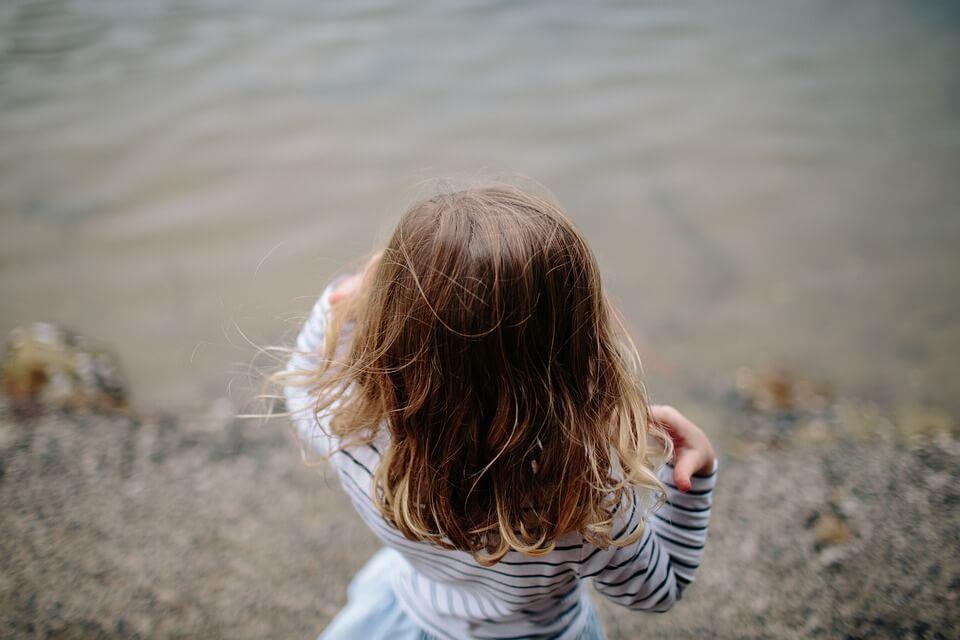 Bambina di spalle davanti all'acqua