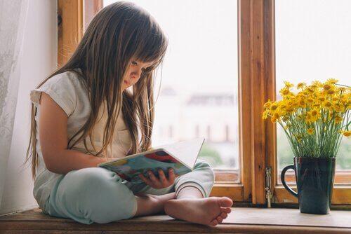 Bambina legge seduta alla finestra
