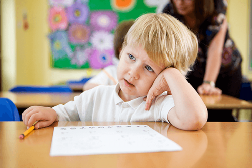 Bambino distratto durante la lezione a scuola