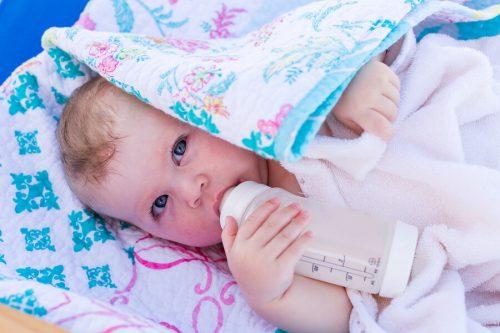 Bambino prende il biberon protetto dal sole