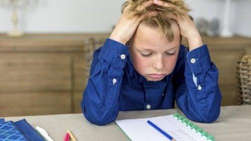 Bambino si mette le mani nei capelli mentre fa i compiti