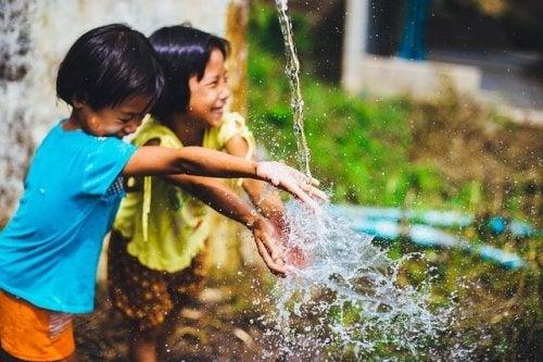 Bambini estroversi che giocano con l'acqua