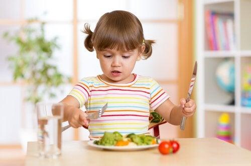 Bambina mangia con le posate un piatto di verdure