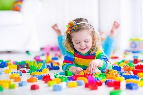 Bambina gioca da sola con le costruzioni