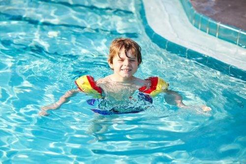 Bambino in piscina con i braccioli