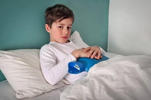Bambino a letto con una borsa dell'acqua calda sulla pancia
