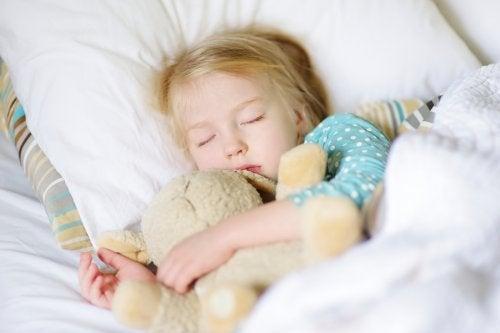 Bambina che dorme con peluche
