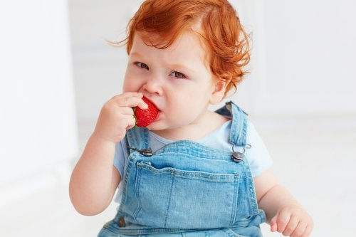 Bambino che mangia una fragola