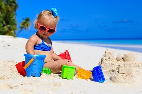 Bimba in spiaggia fa i castelli di sabbia