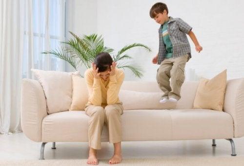 Bambino che salta sul divano con mamma
