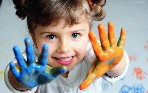 bambina con vernice sulle mani