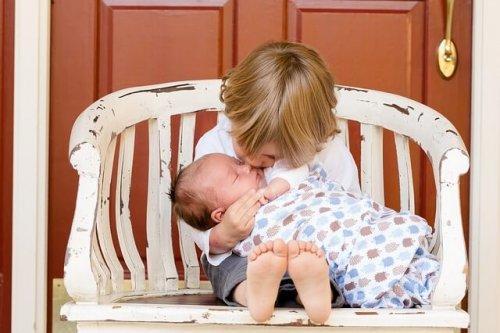 Bambino con fratellino in braccio