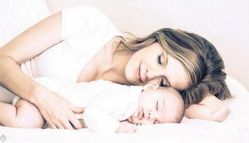 Mamma sdraiata con neonato