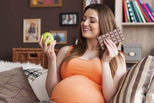 donna incinta con mela e cioccolato