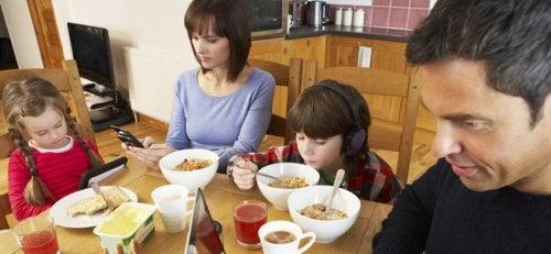 famiglia che usa la tecnologia a tavola