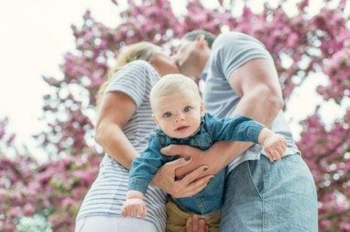 genitori che si baciano con figlio in braccio