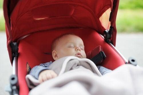 Neonato che dorme nel passeggino