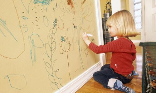 bambina che disegna sul muro con pennarello