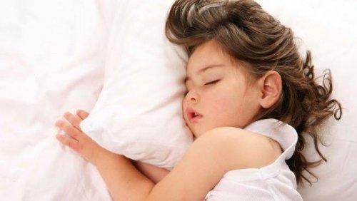 bambina che dorme sui cuscini