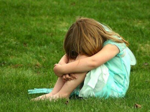 bambina con la testa bassa in mezzo al prato
