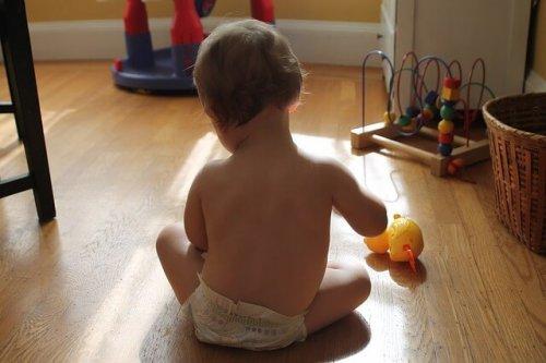 bambino con pannolino che gioca sul pavimento
