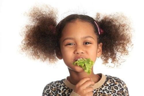 Bambina che mangia insalata