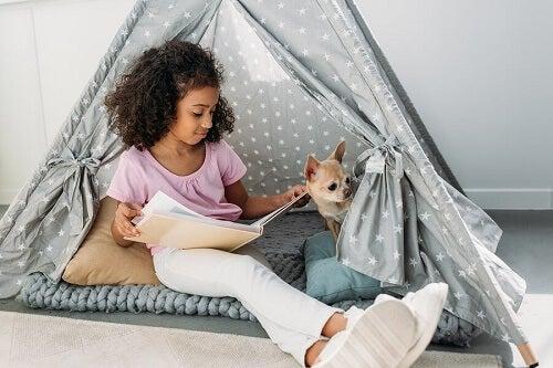 bambina di colore su amaca legge libro con chihuahua accanto
