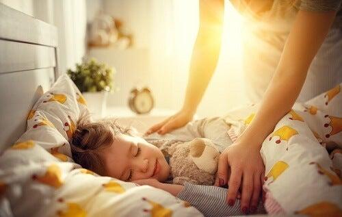 bambina dorme nel letto con la mamma sopra