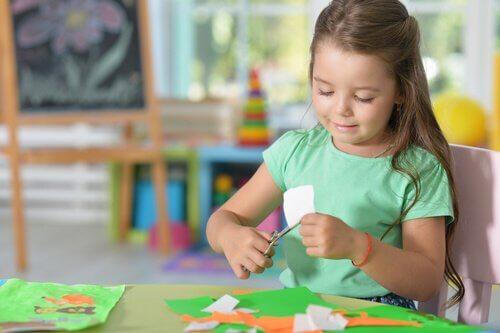 bambina taglia un cartoncino seduta