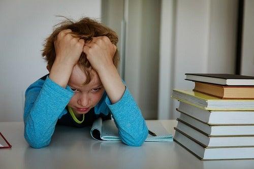 bambino con mani nei capelli accanto a libri