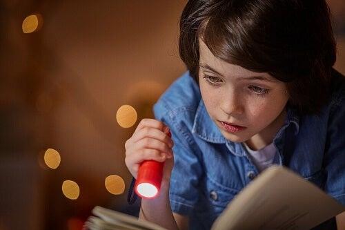 bambino legge libro con torcia