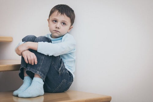 bambino triste seduto su scala di legno