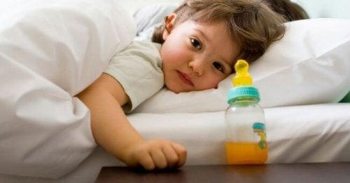 bimba a letto di lato con tazze con succo d'arancio
