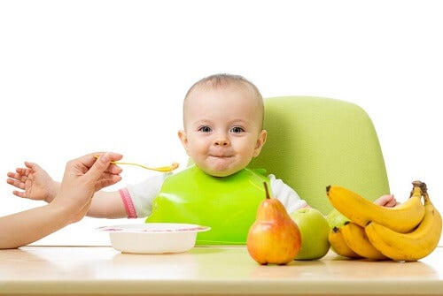 bimbo mangia pappina seduto con accanto banane