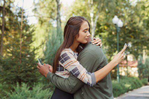 coppia di fidanzati abbracciati scrive su smartphone