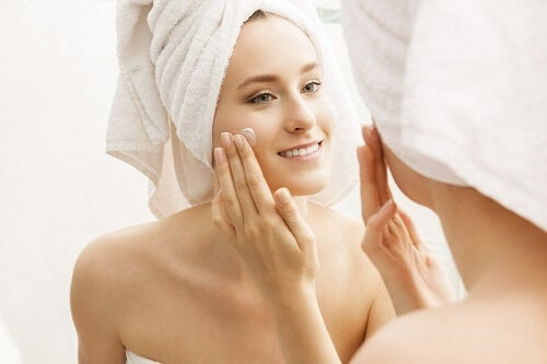 donna si mette crema viso davanti a specchio
