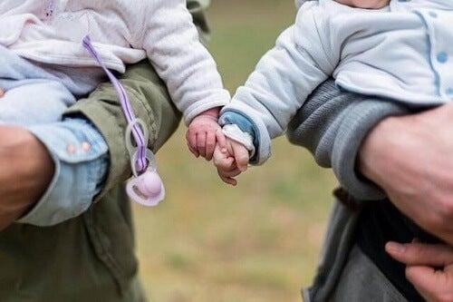 due neonati tenuti in braccio si toccano le mani