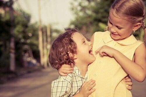 fratellino e sorellina scherzano abbracciati in strada