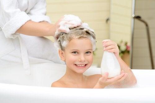 madre lava i capelli al bambino nella vasca