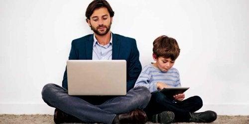 padre e figlio seduti vicini giocano con il computer