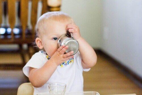 piccola bimba beve da una tazza di metallo