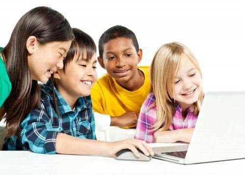 quattro ragazzi sorridono davanti a pc portatile bianco